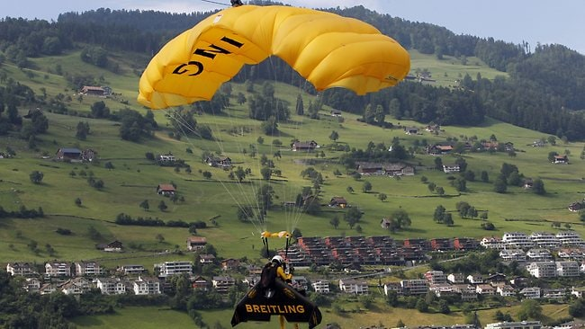 Yves Rossy parachuting down to land on Buochs Airport, Switzerland after the stunt. Picture: Urs Flueler/Photopress via AP Images