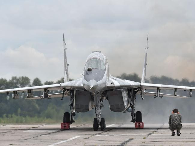 A technician looks at a Ukrainian MIG-29 fighter prior to taking off during exercises at the air force military base in the small town of Vasylkiv last month. Picture: Sergei Supinksy