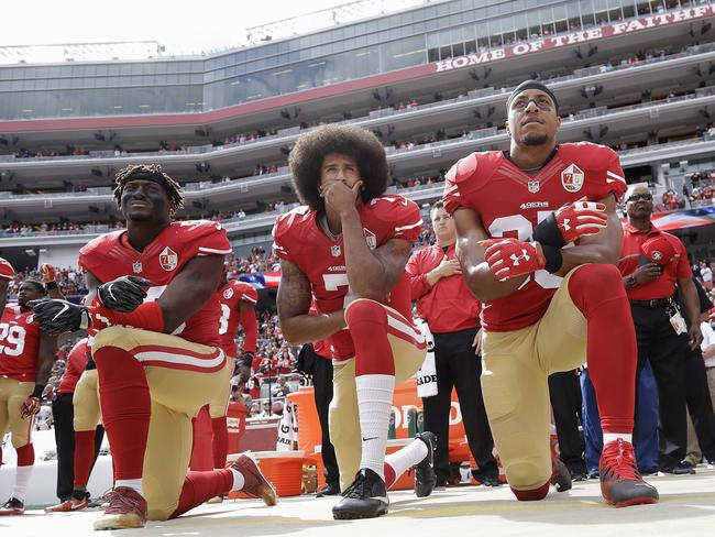 Colin Kaepernick, along with 49ers teammates Eli Harold (left) and Eric Reid (right), kneel in protest during the national anthem.