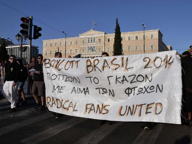 "Youths hold a banner reading ""Brazil 2014 - they water the grass with the blood of the poor"" as they demonstrate in solidarity with the poor of Brazil and call for a boycott of the FIFA World Cup."