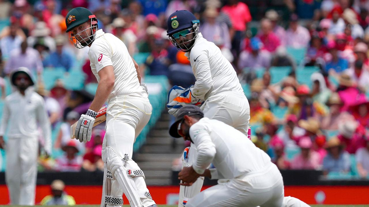 Australia's Shaun Marsh (L) glances behind as he is caught by Ajinkya Rahane during the third day's play of the fourth and final cricket Test in Sydney.