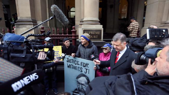 Protesters held placards outside court as Cardinal George Pell was escorted into the Supreme Court of Victoria in Melbourne this morning. Picture: Asanka Brendon Ratnayake/AFP