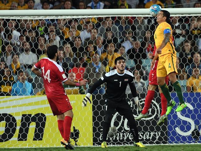 Australia's Tim Cahill heads a ball into Syria's goal.