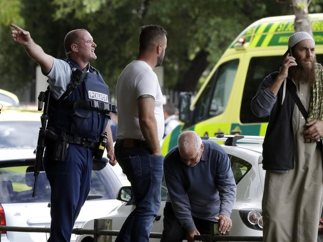 Police attempt to clear people from outside a mosque in central Christchurch, New Zealand, Friday, March 15, 2019. (AP Photo/Mark Baker)