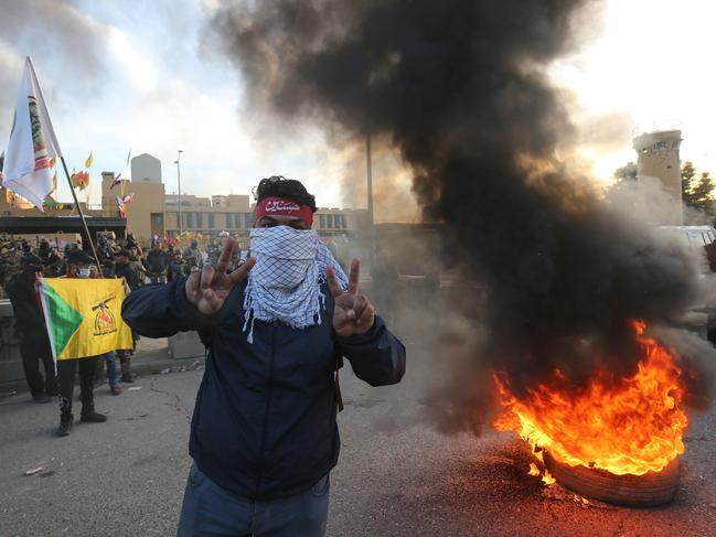 A supporter of Iraq's Hashed al-Shaabi paramilitary force flashes victory signs during a protest outside the US embassy. Picture: Ahmad Al-Rubaye/AFP
