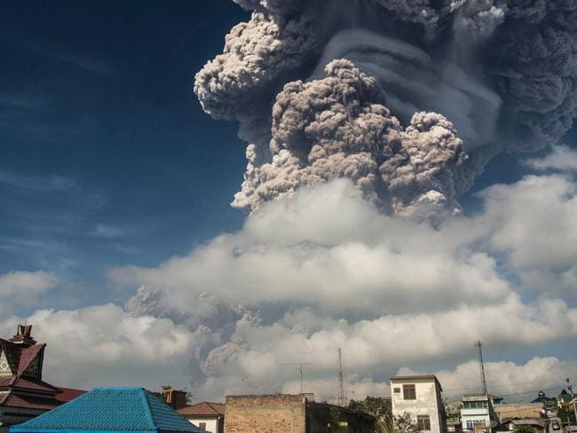 Sinabung sent ash and smoke 5,000 metres into the air, leaving local villages coated in debris and officials scrambling to hand out face masks. Picture: AFP