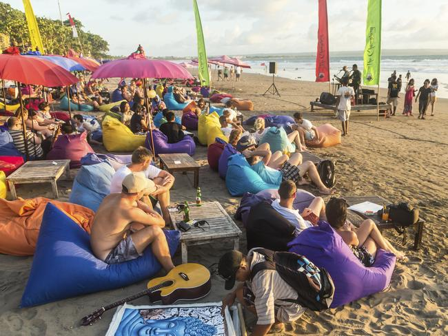 Bali's beach bars are a magnet for tourists. Pictured, drinking on Seminyak beach before sunset.