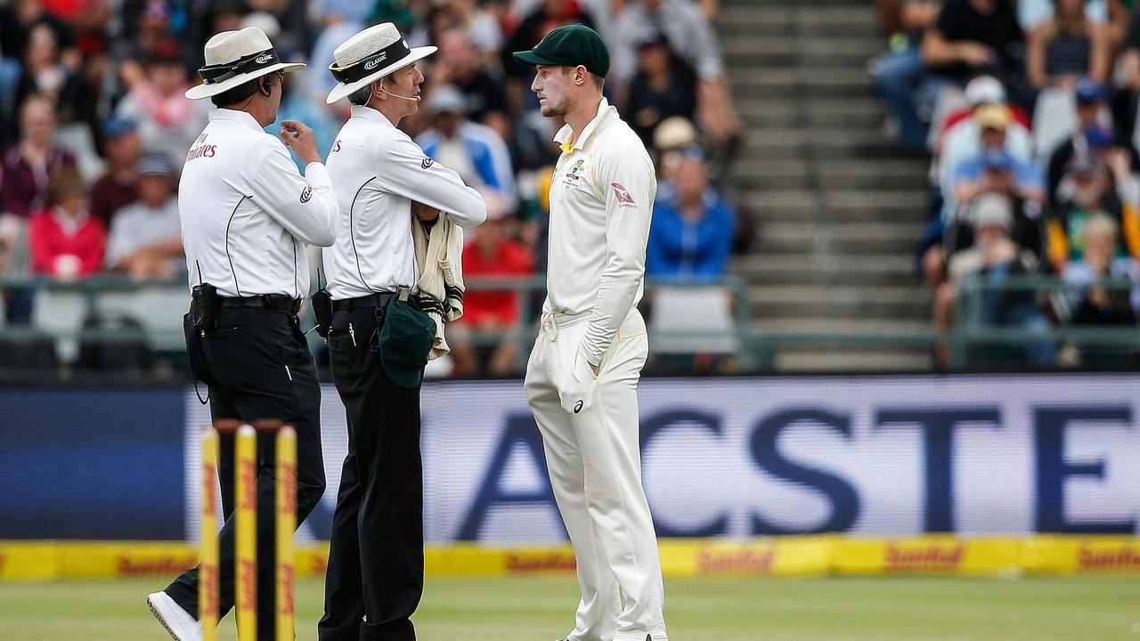 Cameron Bancroft (R) is questioned by Umpires Richard Illingworth (L) and Nigel Llong (C) during day three at Newlands on March 24, 2018.