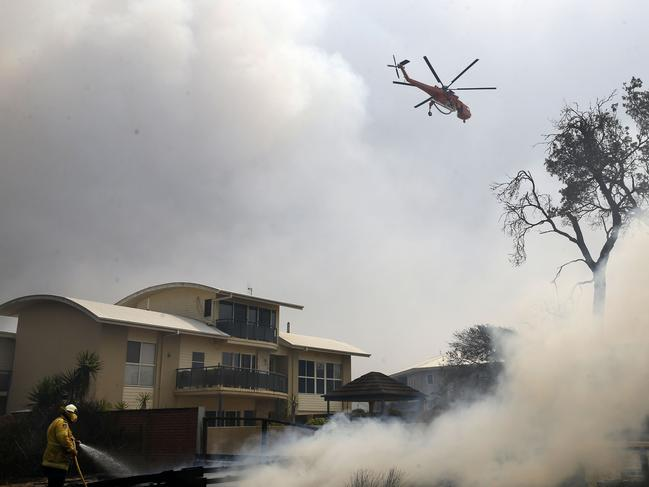 A fire bombing helicopter works to contain a bushfire along Old Bar road in Old Bar, NSW, Saturday, November 9, 2019. Two people have been killed and seven others are missing in bushfires in NSW which have also destroyed at least 100 homes. (AAP Image/Shane Chalker)