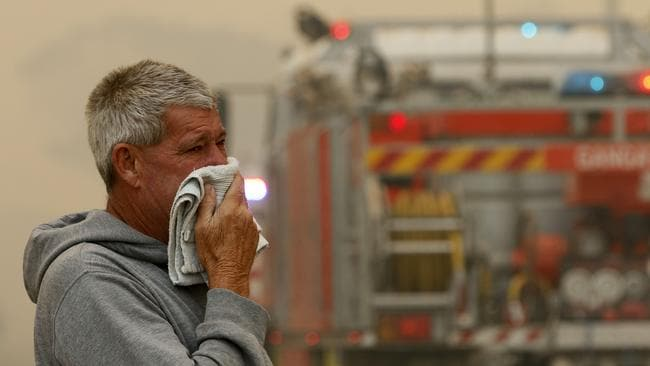 A resident watches the progress of bushfires near houses in Old Bar, NSW on Saturday. Picture: Shane Chalker/AAP