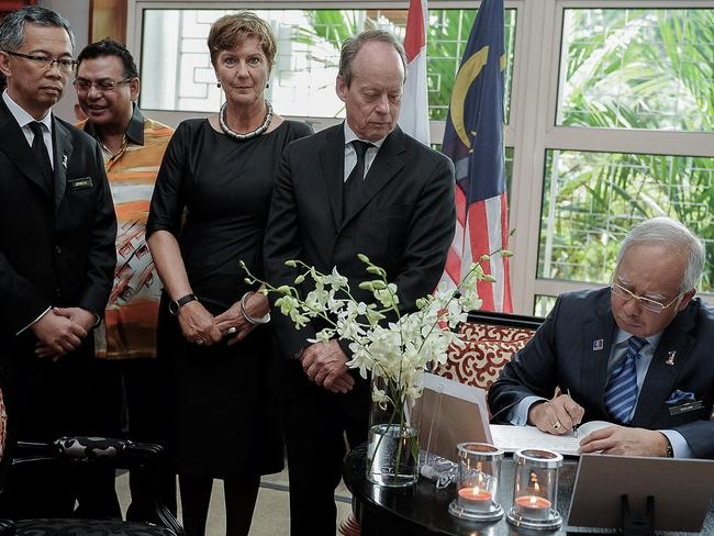 To visit Amsterdam ... Malaysia's Prime Minister Najib Razak (right) signs a condolence book for victims of Malaysia Airlines flight MH17 as Dutch Ambassador Harry Molenaar (2nd, right).
