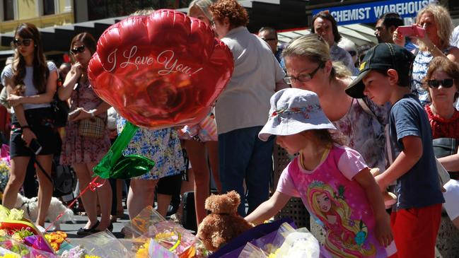 Members of the public laying flowers and touching tributes at a public memorial site for the Bourke St tragedy last year. Picture: David Crosling