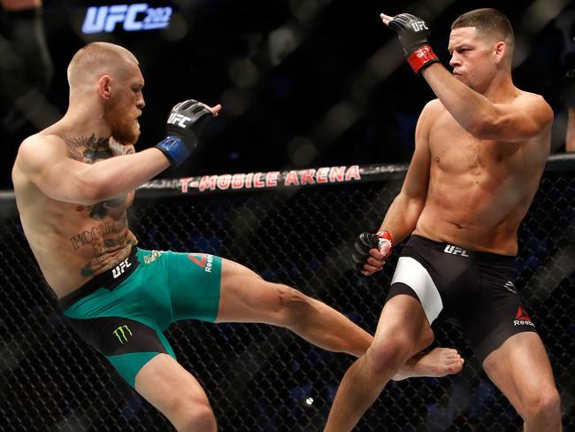 Conor McGregor (L) kicks Nate Diaz during UFC 202.