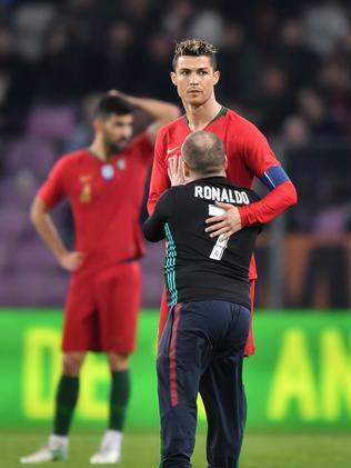 A pitch invdaing fan hugs Portugal's forward Cristiano Ronaldo during the international friendly football match between Portugal and Netherlands