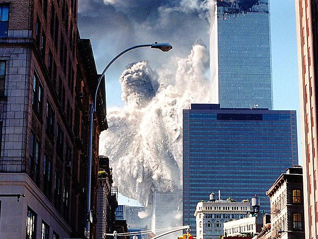 People watch as the towers collapse.