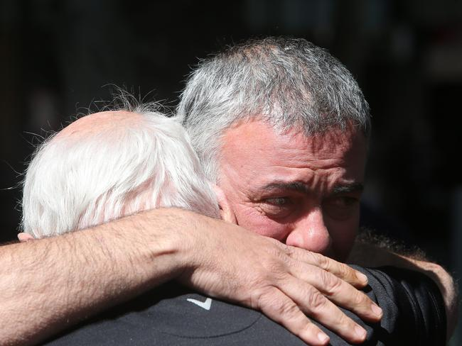 Nino Pangrazio, the business partner of murder victim Sisto Malaspina, hugs a friend near Pellegrini's Bar after learning of the tragedy. Picture: Yuri Kouzmin