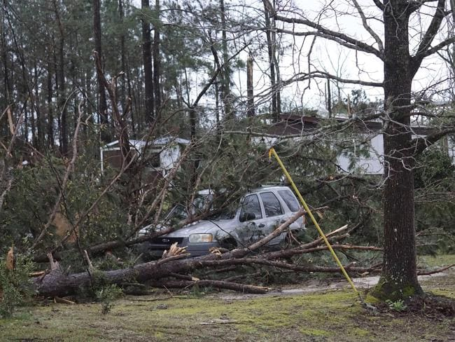 A vehicle is caught under downed trees along Lee Road 11 in Beauregard, Alabama. Picture: AP
