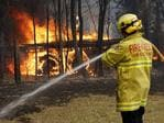 Firefighters work to contain a bushfire along Old Bar road in Old Bar, NSW, Saturday, November 9, 2019. Two people have been killed and seven others are missing in bushfires in NSW which have also destroyed at least 100 homes. (AAP Image/Darren Pateman)