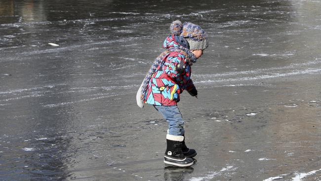 A young child walks on the frozen Prinsengracht canal in downtown Amsterdam. Picture: AP