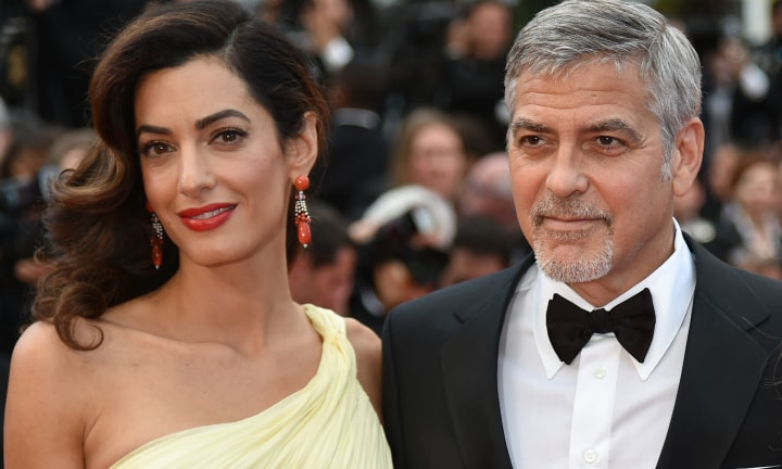 "US actor George Clooney (R) and his wife, British-Lebanese lawyer Amal Clooney pose on May 12, 2016 as they arrive for the screening of the film ""Money Monster"" at the 69th Cannes Film Festival in Cannes, southern France. / AFP PHOTO / ALBERTO PIZZOLI"