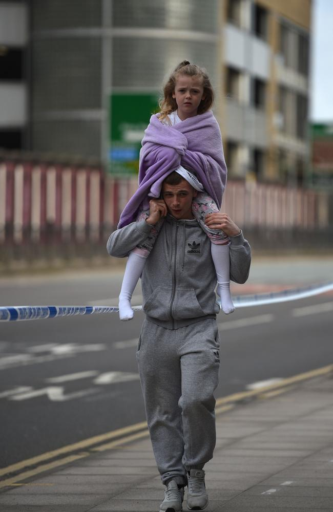 A man carries a young girl on his shoulders after a bombing at an Ariana Grande concert in Manchester in which 22 were killed. Picture: AFP Photo/Oli Scarff