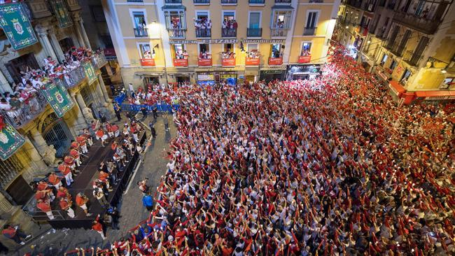 Revellers raise red scarves and candles as they sing the song 'Pobre de Mi', marking the end of the San Fermin festival in Pamplona, northern Spain. Picture: Ander Gillenea/AFP
