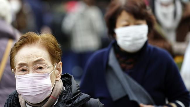 Pedestrian wear protective masks as they walk in a shopping district in Tokyo after a man returning from China tested positive for the new coronavirus linked to SARS. Picture: AP