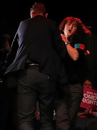 The protester is dragged off stage by security. Picture: Kym Smith