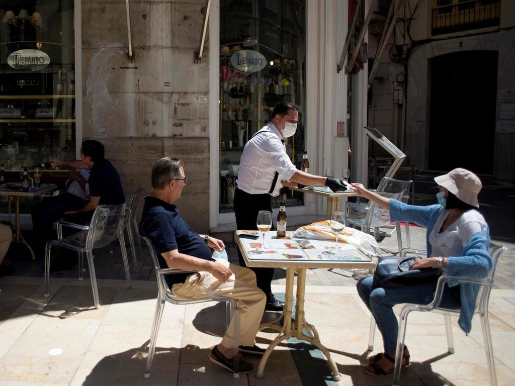 A waiter charges customers at a terrace bar in Malaga. Last week, Spain began a three-phase plan to end lockdowns for half the country by the end of June. Picture: AFP