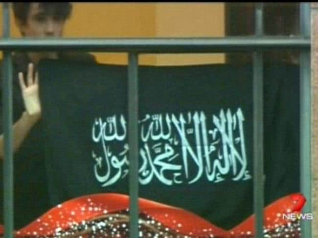 Jarrod Hoffman is seen holding a flag with Islamic script on Seven News.