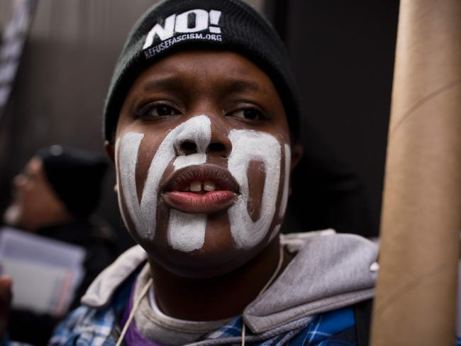 "A woman with the word ""No!"" painted on her face protests outside Trump Tower in New York City. Picture: AFP / Dominick Reuter"