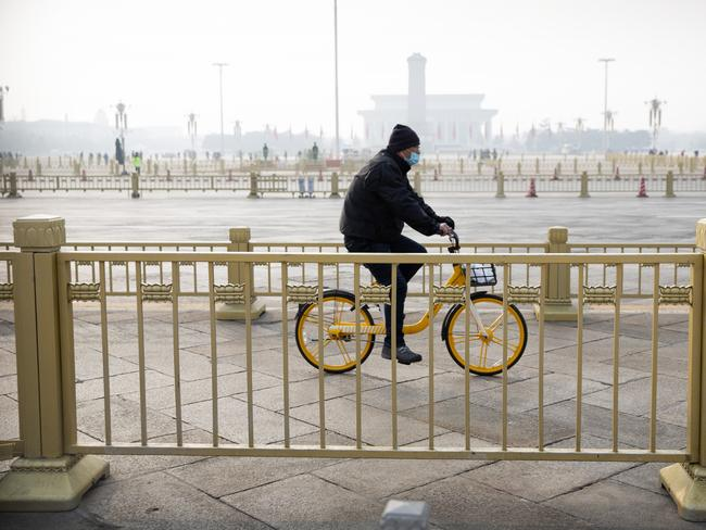 A man rides his bike past normally crowded Tiananmen Square in Beijing. Picture: AP Photo/Mark Schiefelbein.