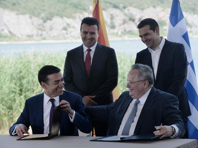 Greek Foreign Minister Nikos Kotzias (down, R) and his Macedonian counterpart Nikola Dimitrov (down, L) sign a preliminary accord as Greek Prime Minister Alexis Tsipras (R) and Macedonian Prime Minister Zoran Zaev stand behind. Picture: AFP