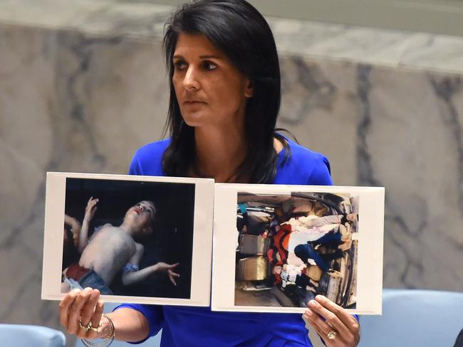 US Ambassador to the UN, Nikki Haley holds photos of victims as she speaks as the UN Security Council meets in an emergency session at the UN yesterday. Picture: Timothy A Clary/AFP