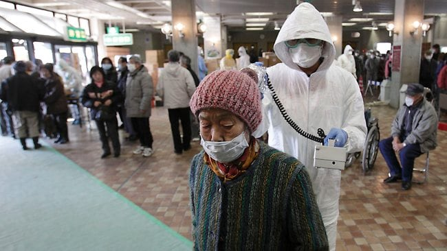 EXPOSURE CHECK: A woman is scanned for radiation exposure at a temporary scanning center for residents living close to the quake-damaged Fukushima Dai-ichi nuclear power plant in northern Japan.