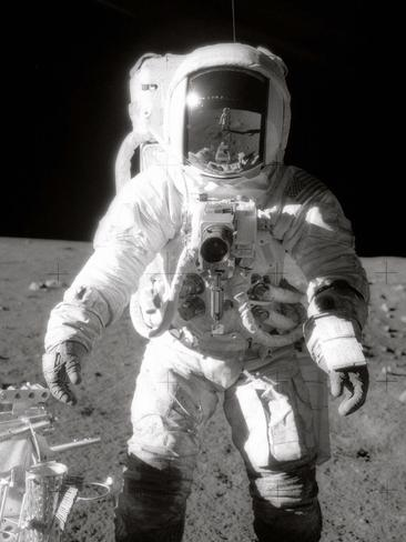 Astronaut Alan L. Bean near a tool carrier during extravehicular activity (EVA) on the Moon's surface. Commander Charles Conrad Jr., who took the black and white photo, is reflected in Bean's helmet visor.