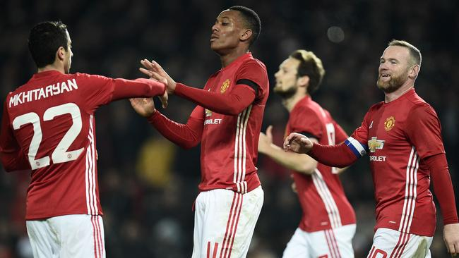 Anthony Martial (2L) celebrates with midfielder Henrikh Mkhitaryan (L) and Wayne Rooney.