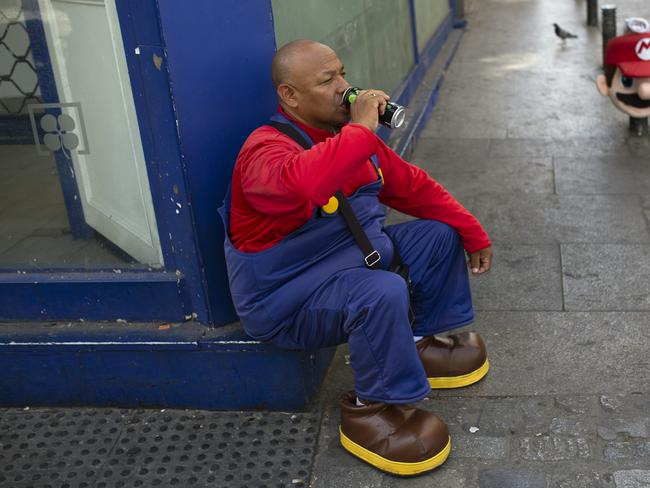 A man wearing a Mario Bros costume takes a break from work posing for tourist photos in the shade at Sol square in Madrid. Picture: Francisco Seco
