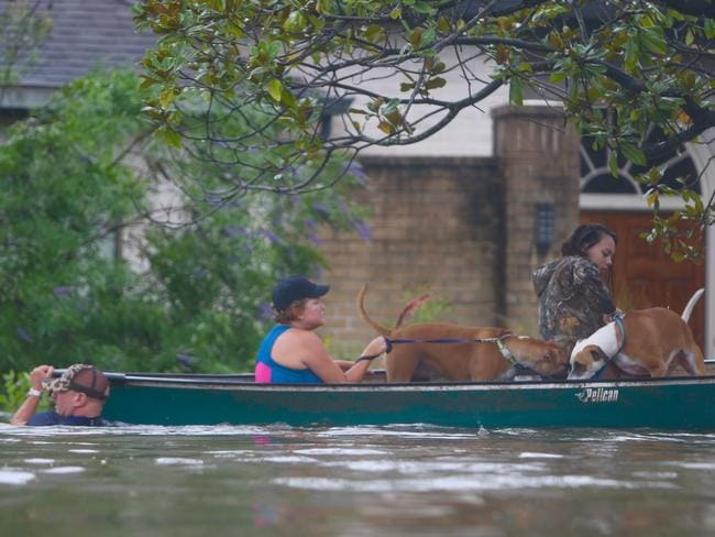 A family evacuates their Meyerland home in Houston on Sunday. Picture: Mark Mulligan/Houston Chronicle via AP