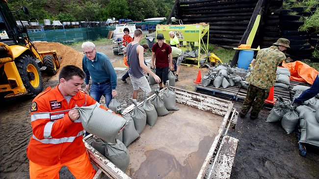 Volunteers fill and load sandbags at the Ipswich SES. Picture: Mark Calleja