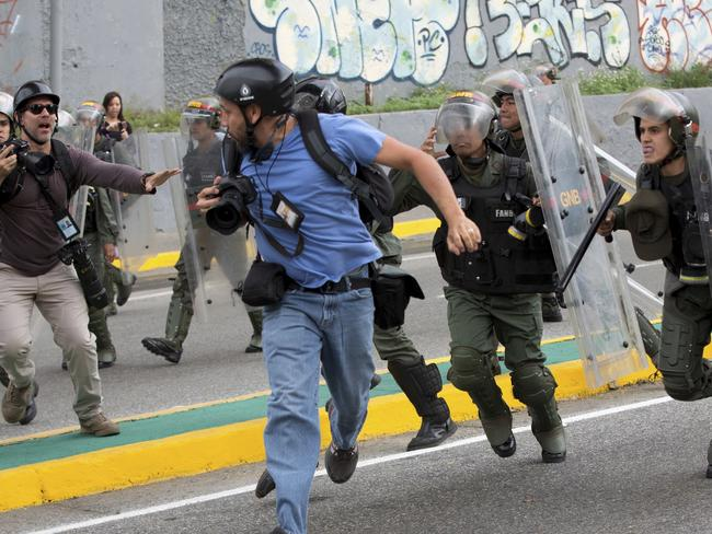 Reuters photojournalist Marco Bello runs as Venezuelan National Guard soldiers chase him during a protest outside the Supreme Court in Caracas, Venezuela. Picture: AP
