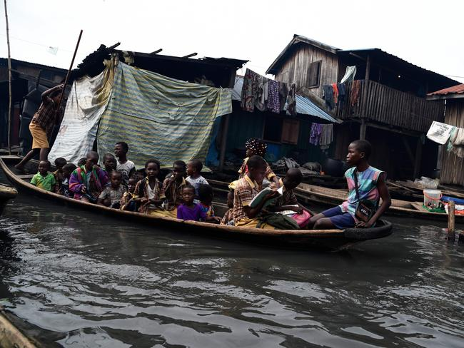 Children sit in a canoe on their way home from school in Makoko. (Photo by PIUS UTOMI EKPEI / AFP)