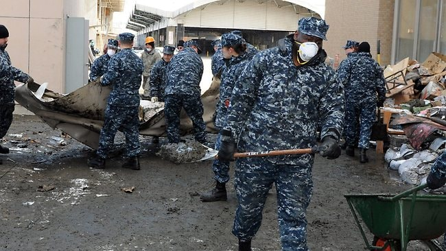 A US Navy handout image made available 17 March 2011 showing Logistics Specialist 2nd Class Robert Bannister, from Chicago, assigned to Fleet and Industrial Supply Center Misawa, removing sediment 17 March 2011 from behind a damaged building. Sailors from Naval Air Facility Misawa and its tenant commands are assisting with the clean up of the tsunami-damaged city. Picture: US Navy/Devon Dow