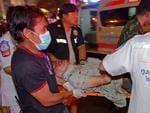 An injured man is rushed to a waiting ambulance. AFP PHOTO / PORNCHAI KITTIWONGSAKUL