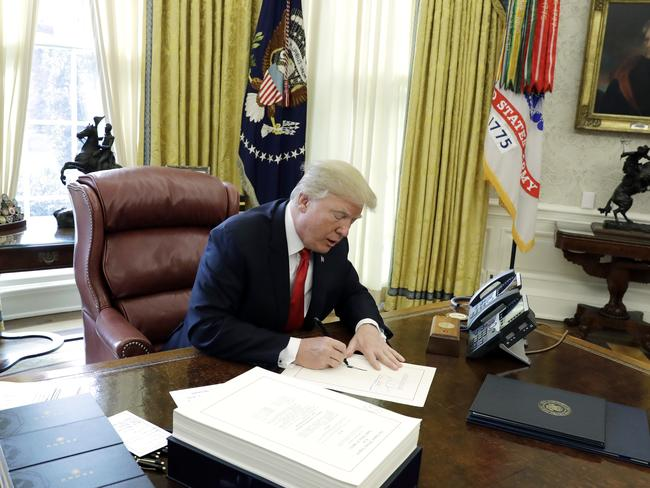 US President Donald Trump signs into law a $1.9 trillion tax overhaul package in the Oval Office of the White House in Washington. Picture: AP