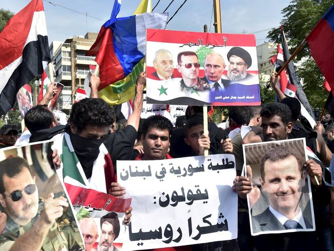 Syrians, living in Lebanon, carry banners as they wave Russian and Syrian national flags to express their support to Syria's President Bashar al-Assad and to thank Russia for its intervention in Syria, outside the Russian embassy in Beirut, Lebanon.