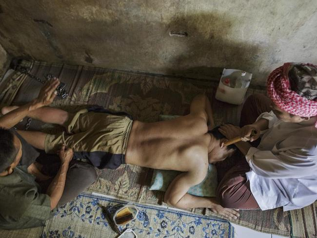 An Islamic faith healer chants as his assistant slaps the leg of a man at the Pengobatan Alternaif Nurul Azha centre in West Java. Picture: Andrea Star Reese/Human Rights Watch.