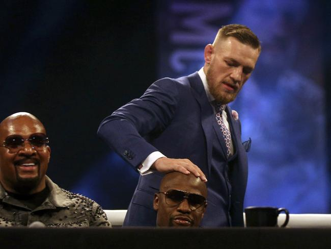 Irish boxer Connor McGregor, background, touches US boxer Floyd Mayweather Jr on the head.