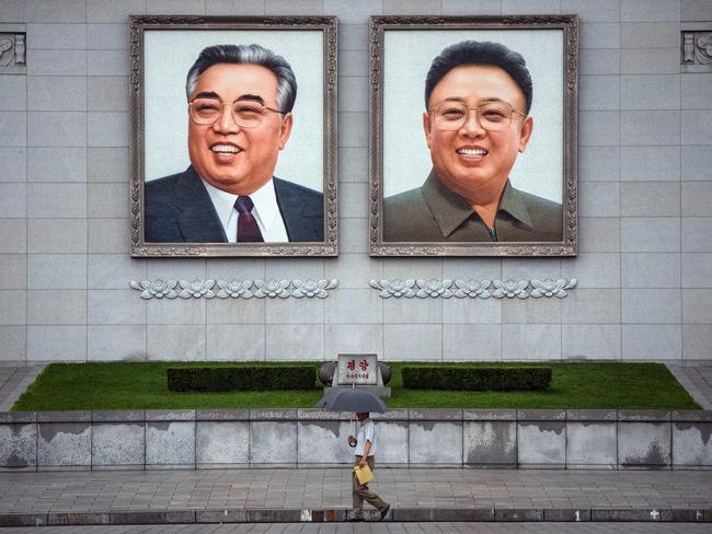 People walk beneath huge pictures of Kim Il-sung and Kim Jong-il displayed from the Parade Reviewing Stand in Kim Il-sung Square. Picture: Carl Court/Getty Images