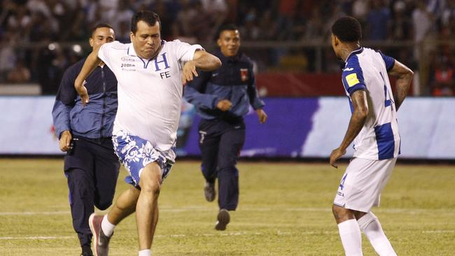 A Honduras fan is chased by security guards after he invaded the pitch during a World Cup qualifying soccer match against Mexico, in San Pedro Sula, Honduras.